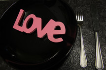 "Pink letters spelling ""love"" on a black plate at a place setting."