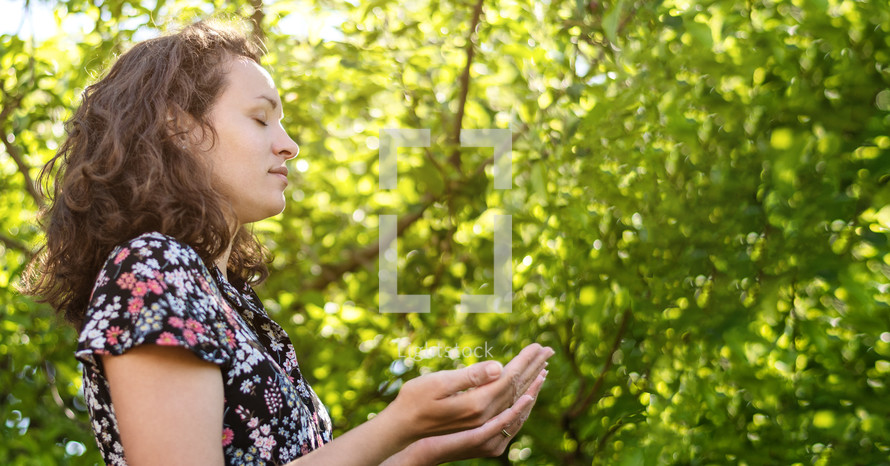 Christian worship and praise. A young woman is praying and worshiping in the evening. Worship and prayer banner.