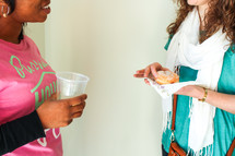 women talking while eating donuts
