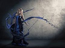 A woman in a blue dress with abstract paint splatters.