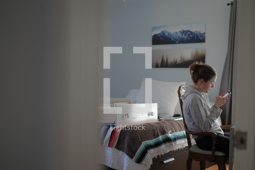 a woman in chair texting and empty drawers on a bed