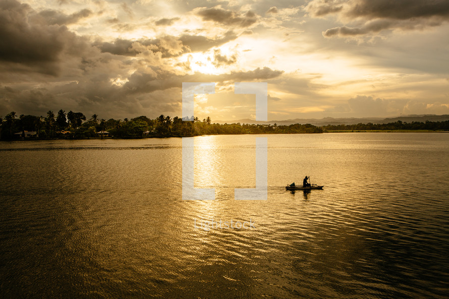 a man paddling in a boat on a river at sunset