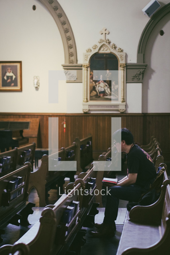 A man praying the Stations of the Cross in a Catholic church