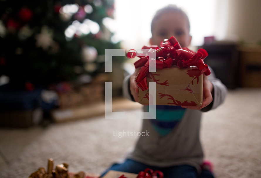 a child holding out a Christmas present