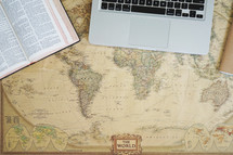 Bible, laptop, and journal on a world map