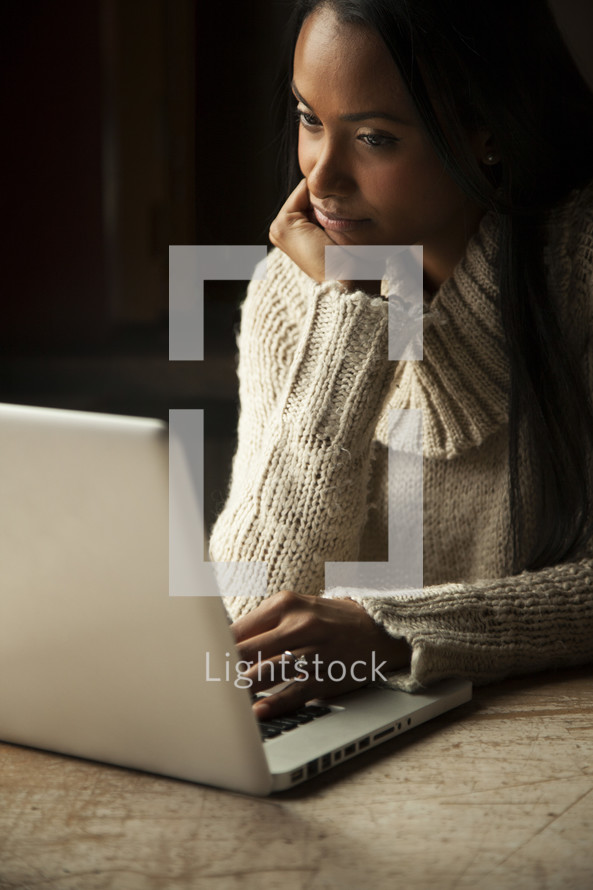 a woman sitting in front of a laptop computer