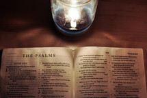 Bible open to The Psalms on a wooden table near a burning candle.