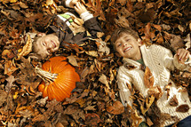 boys lying in a leaf pile