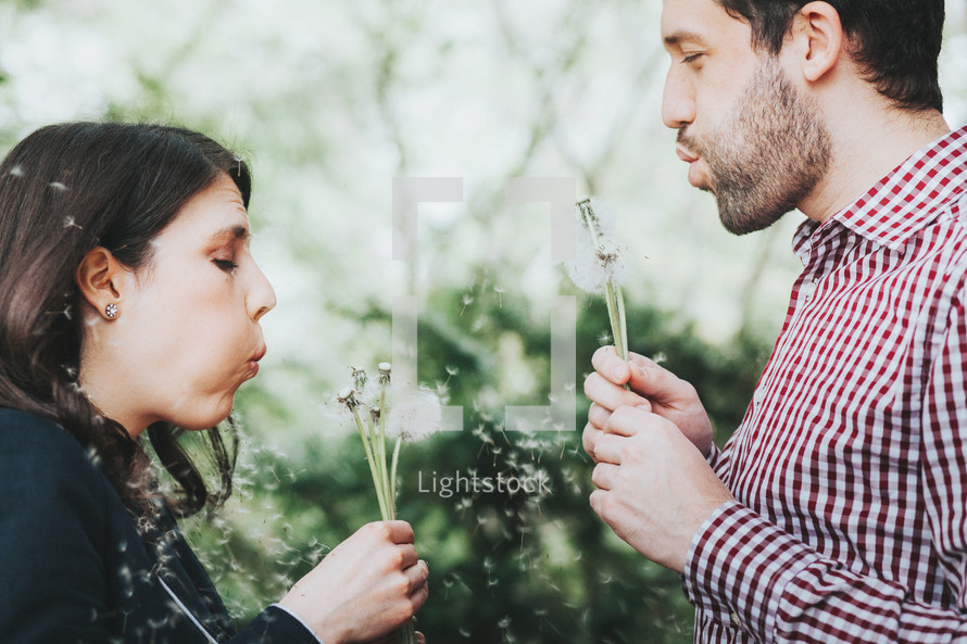 man and woman blowing dandelions