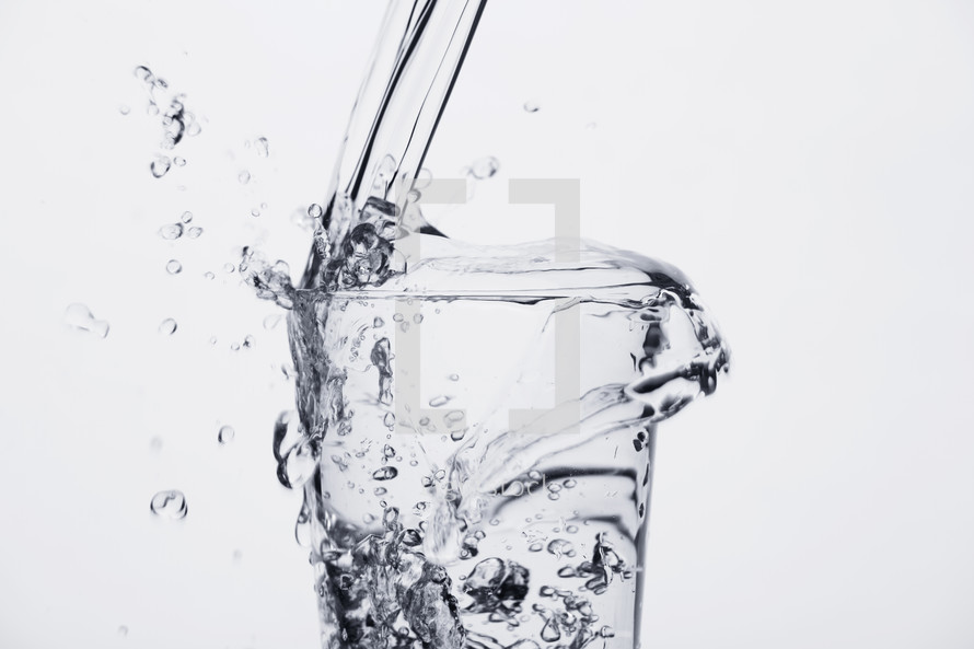 Glass cup overflowing with fresh water.