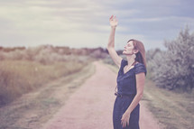 woman standing on a dirt road with her hand raised praising God