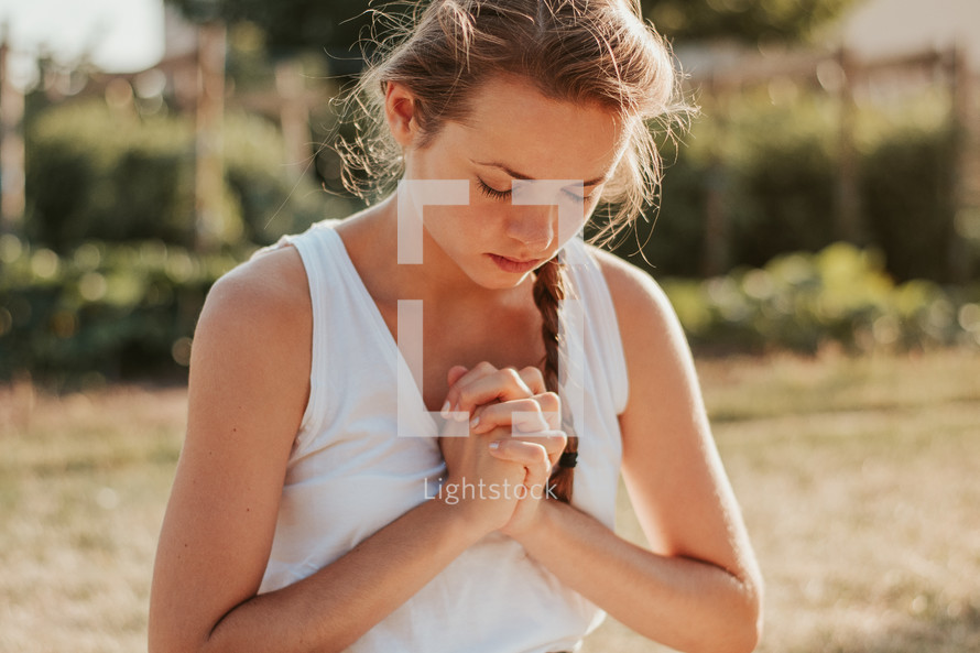 a woman praying outdoors