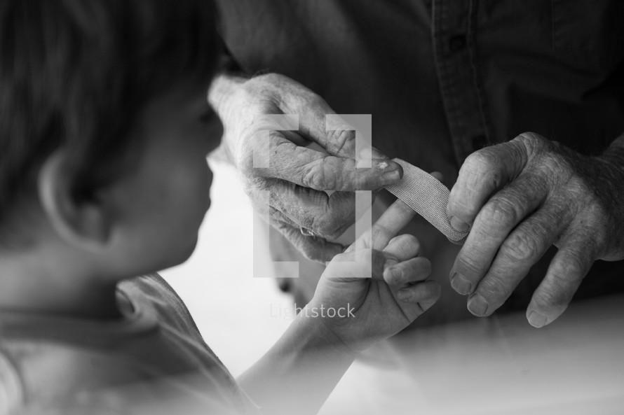 a grandfather placing a bandage on a his grandson's finger