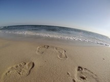 foot prints in the sand leading to the ocean