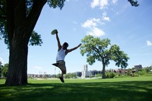 a young man catching a frisbee in a park