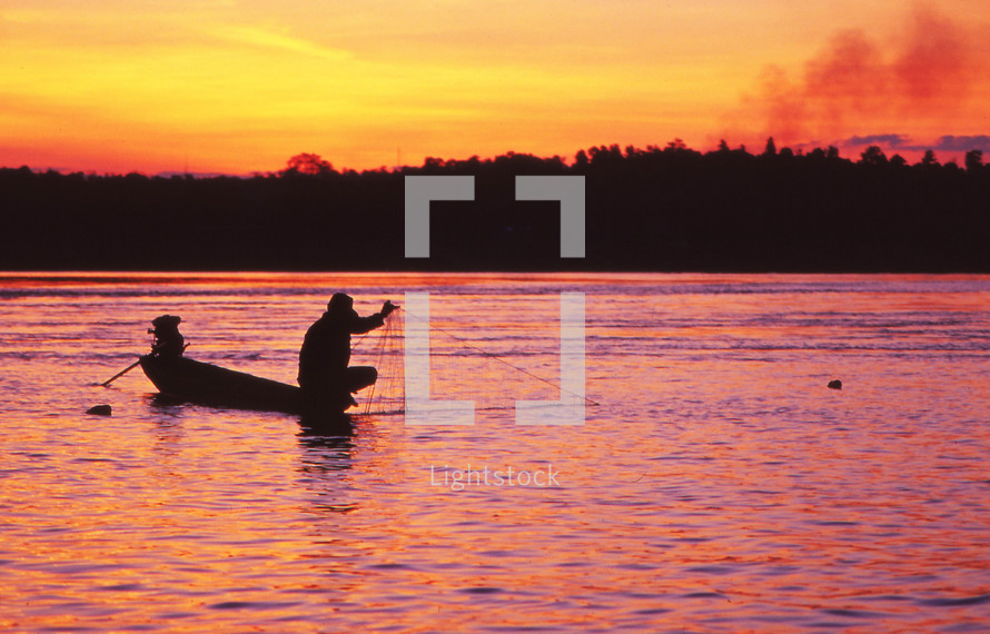 a man fishing with a net from his boat at sunset