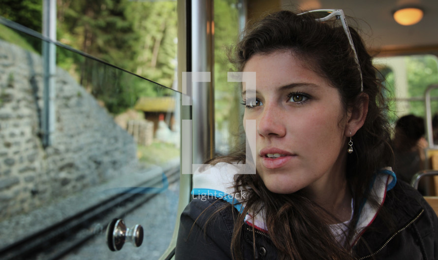 face of a woman looking out a window on a bus