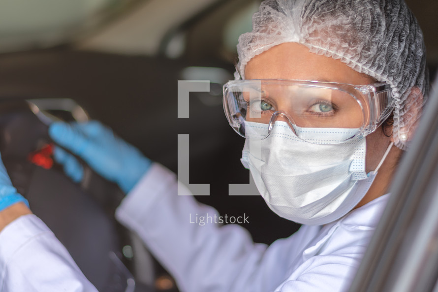 Young doctor or nurse driving car with protective mask on her face. COVID-19. Coronavirus