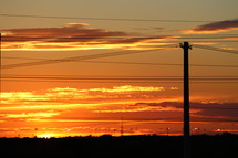 power lines under an orange sky at sunset