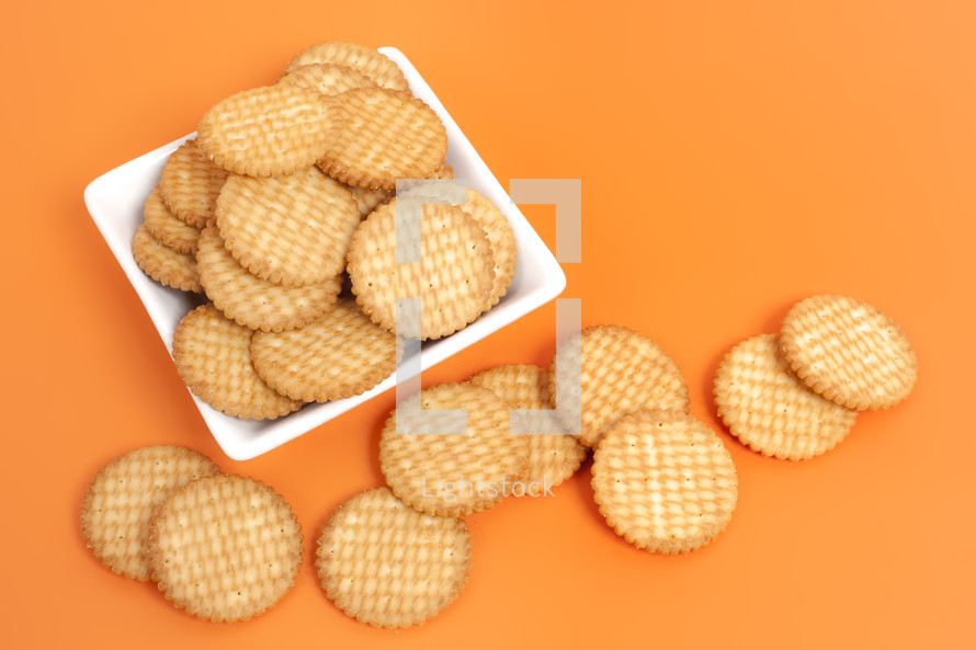 A white plate full of round crackers on an orange surface.