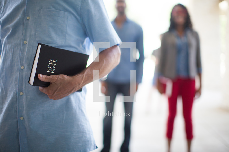men and women standing holding Bibles