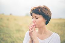 Woman praying outside.