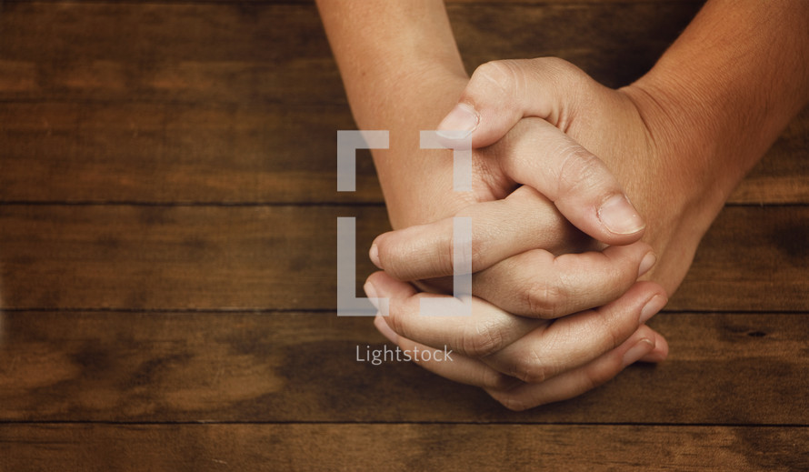 Praying with a wooden background