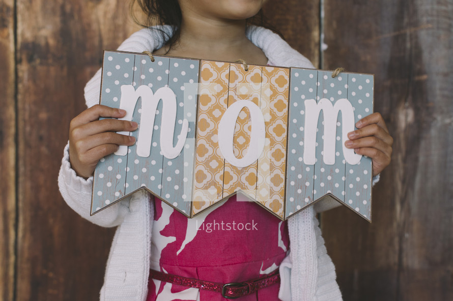 girl child holding a mom sign