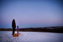 father and daughter sledding at sunset
