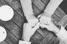 couple holding hands on a wood table