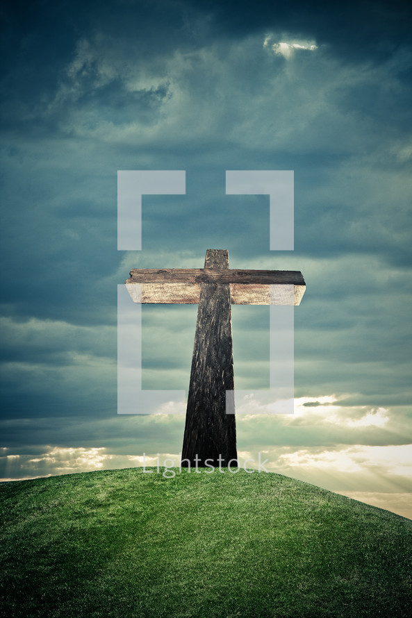 cross on a grassy hill under a cloudy sky