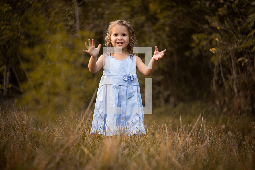 toddler girl standing outdoors with raised hands