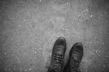 Boots standing on a sidewalk.