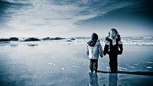 two children in winter coats standing on a beach