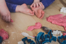 a child plays with playdough and cutter shapes