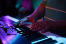 hands playing a digital keyboard