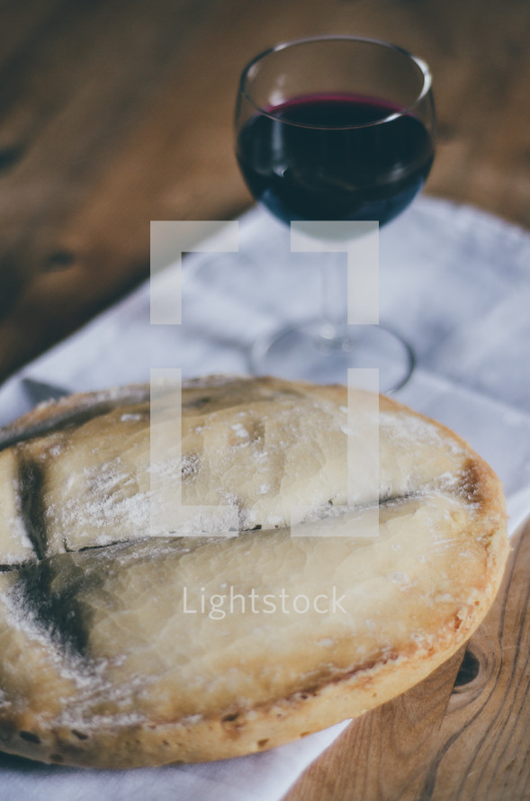 A loaf of bread and a glass of wine on a table