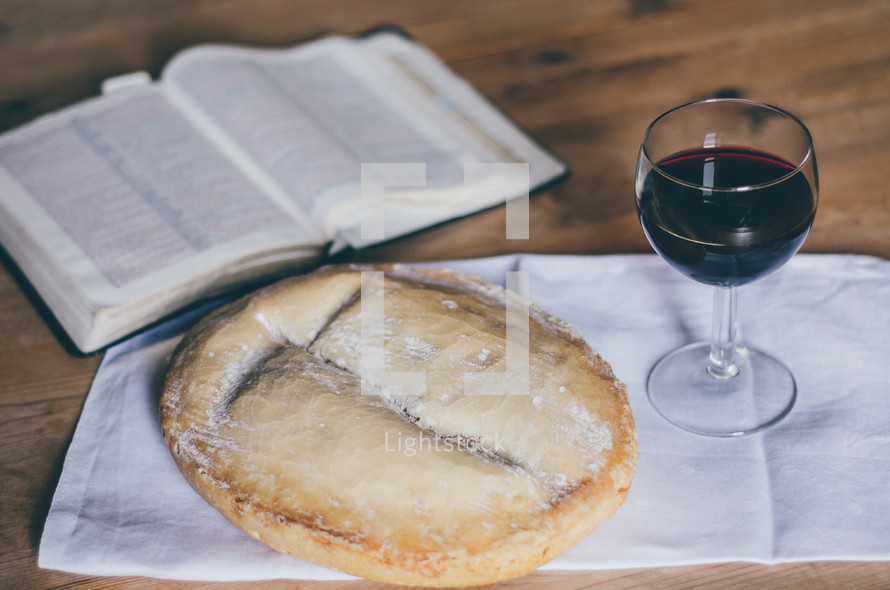 A loaf of bread, open bible, and a glass of wine on a table
