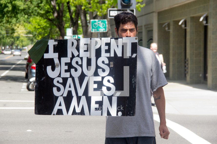 man holding a sign I Repent, Jesus Saves, Amen
