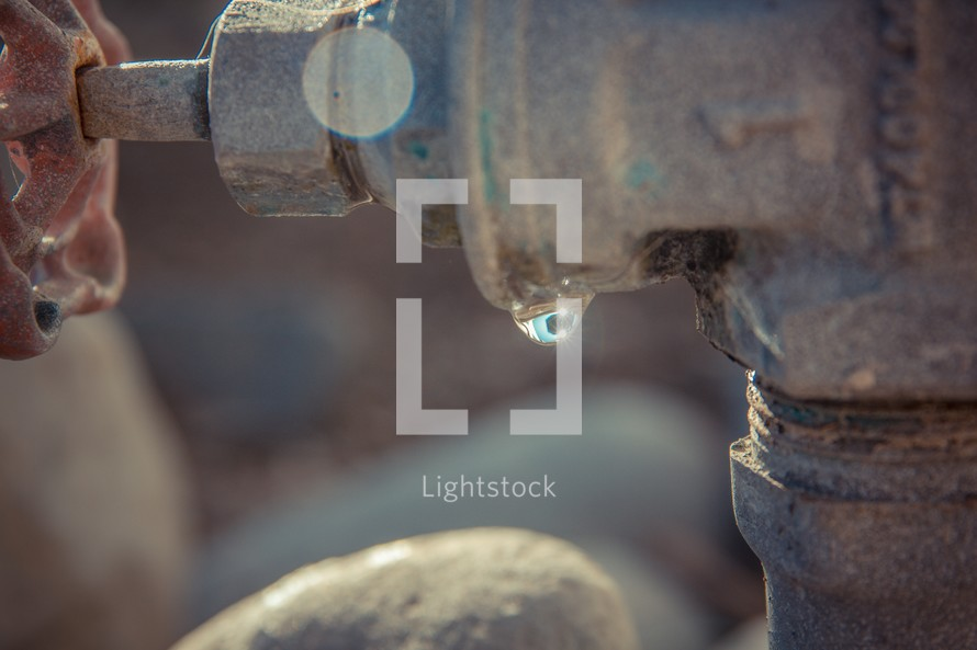 Sun reflecting in waterdrop on a water tap