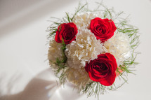 red roses and white carnations in a vase