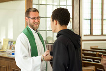 a priest greeting a teen boy