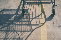 Shadow of a grocery cart reflected on an asphalt road
