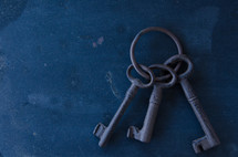 Old ring of keys against grimy background of stains and blemishes.