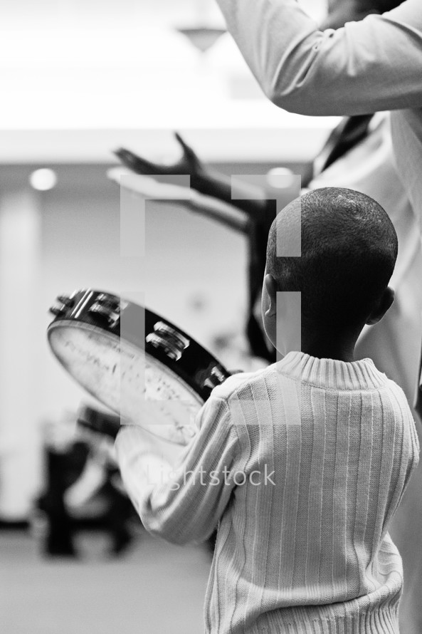 child playing a tambourine at a worship service