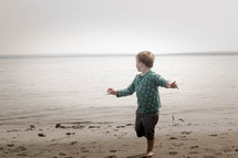 toddler running on a lake shore
