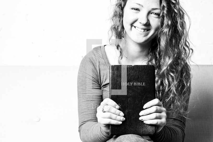 teen girl holding a Bible smiling