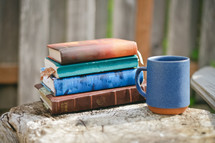 Stack of books and coffee cup on a tree stump.