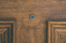 Peep hole in a wooden door.