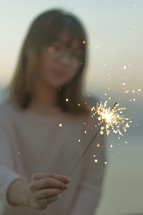 young woman holding a sparkler